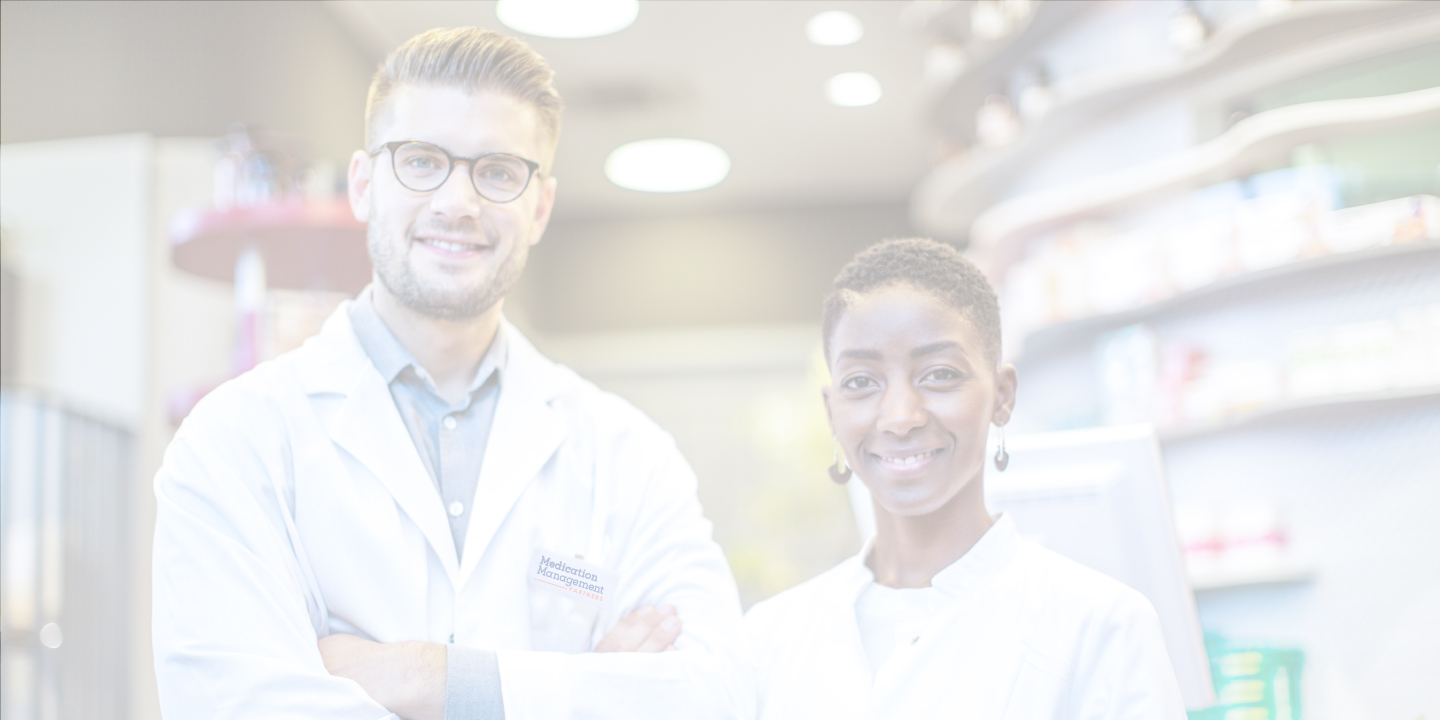 Male and Female pharmacy technicians smiling in front of shelves